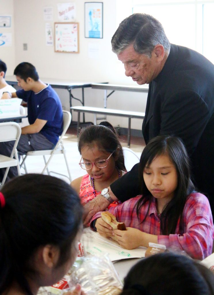 Msgr. Daniel Sullivan checks out what the children are having for lunch after he blessed the Summer Meals Program at Holy Redeemer Camp.