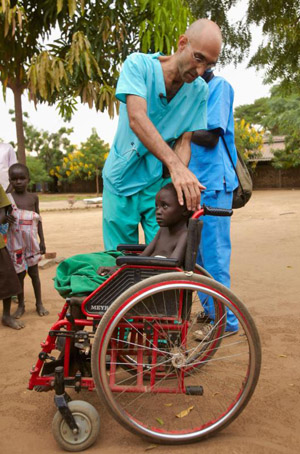 Dr. Tom Catena checks on a young patient in a wheelchair outside Mother of Mercy Hospital in Gidel, Sudan, in 2012. (CNS photo/Jaco Klamer, courtesy CMMB)