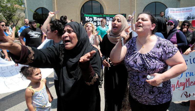 Women react as they talk about family members who were arrested by immigration officials during a June 12 rally outside the Mother of God Chaldean Catholic Church in Southfield, Mich. Dozens of Chaldean Christians were arrested by federal immigration officials over the weekend of June 10 and 11 in the Detroit metropolitan area, which members of the local church community said left them feeling sad and frustrated. (CNS photo/Rebecca Cook, Reuters)