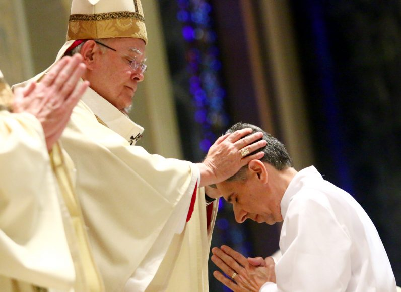 Archbishop Charles Chaput lays hands on the head of Anthony J. Bellitto Jr., ordaining him a deacon for the Archdiocese of Philadelphia.