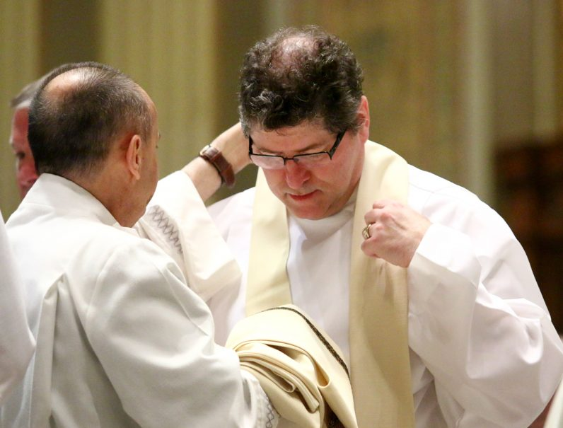 Michael J. Cushing vests as a deacon for the first time.