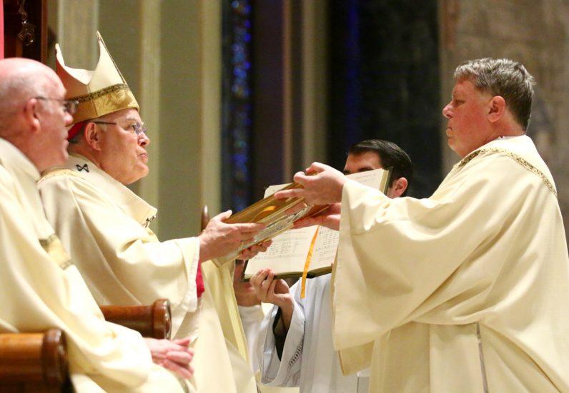 Deacon Mark R. Szewczak receives the Book of Gospels from Archbishop Charles Chaput.