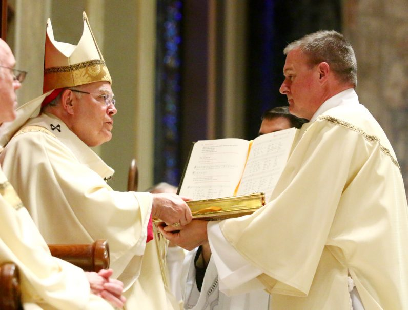 During the ordination rite Archbishop Chaput hands  the Book of Gospels to Deacon Kevin J. Potter.