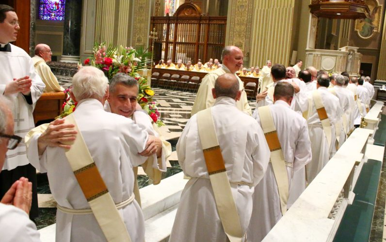 The newly ordained deacons receive a congratulatory fraternal kiss from their brother deacons.