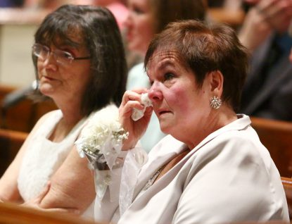 Dianne Kennedy is moved to tears during the ordination rite for her husband Patrick and his classmates.