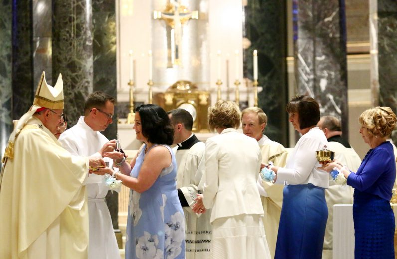 Wives of the newly ordained deacons present the offertory gifts to Archbishop Charles Chaput.