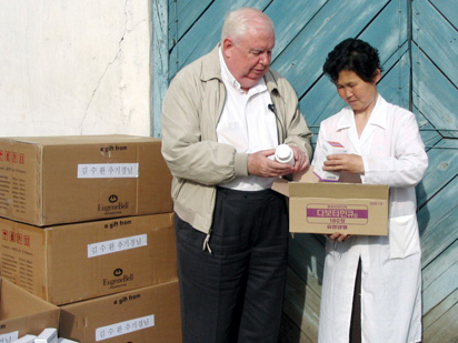 Father Hammond and a nurse check medicine used for distribution to North Korean patients of drug-resistant tuberculosis.