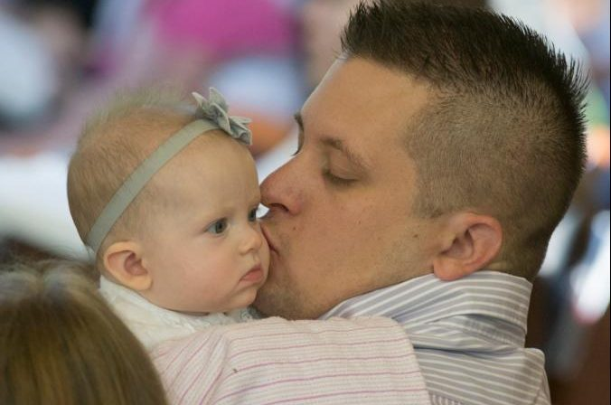 Joseph Niedzielski kisses his 5-month-old daughter, Colette, during a May 18, 2014, Mass at Jesus the Divine Word Church in Huntingtown, Md. God calls fathers to put love into practice in the concrete circumstances of their lives, and true love is a pathway to greater maturity. (CNS photo/Bob Roller)