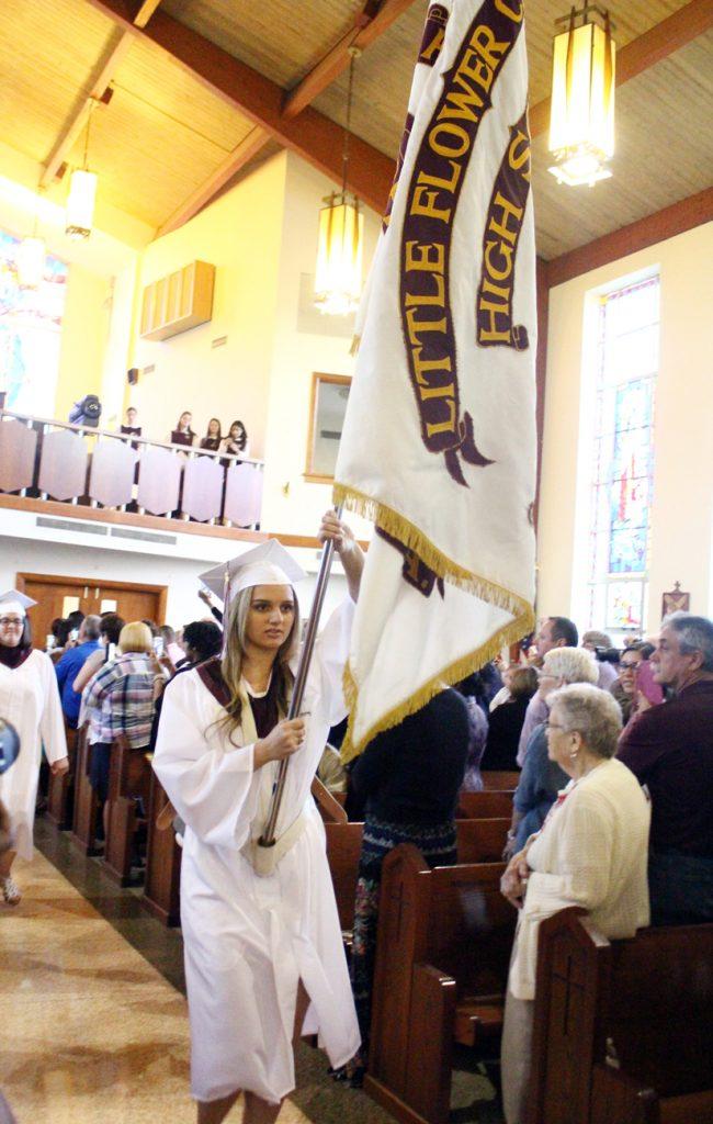 Victoria Fresta carries the Little Flower flag.