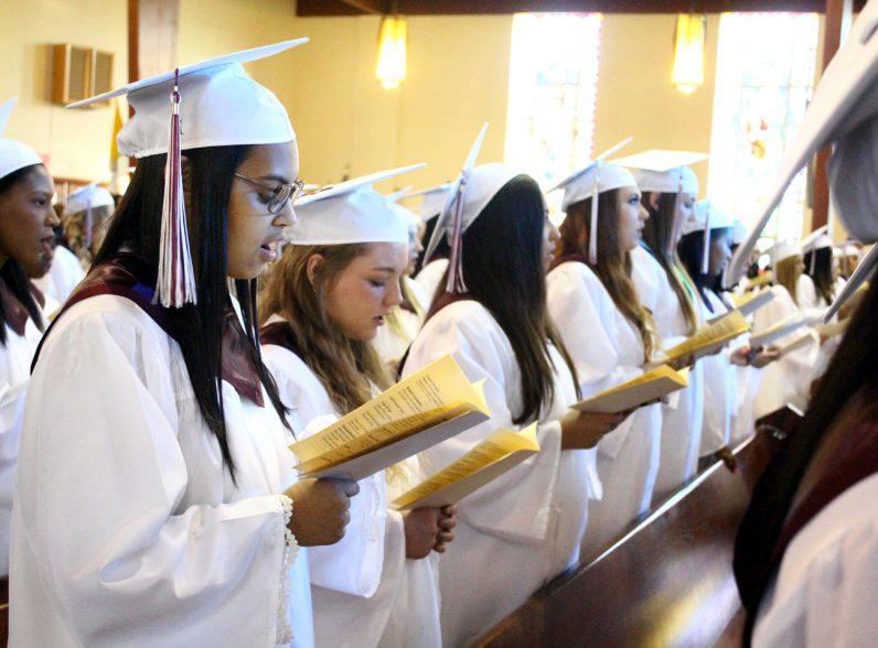 Emily Pineda (left) sings along with fellow Little Flower classmates at their baccalaureate Mass on Thursday, June 8.