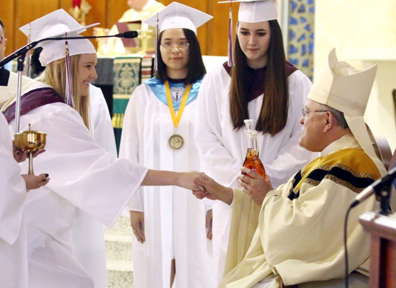 Emily McGovern brings up the wine during the offertory procession at Little Flower High School's baccalaureate Mass Thursday, June 8 at Maternity B.V.M. Church.