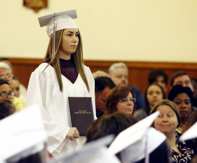 Brianna McKenna carries a diploma to be blessed at Little Flower's baccalaureate Mass.