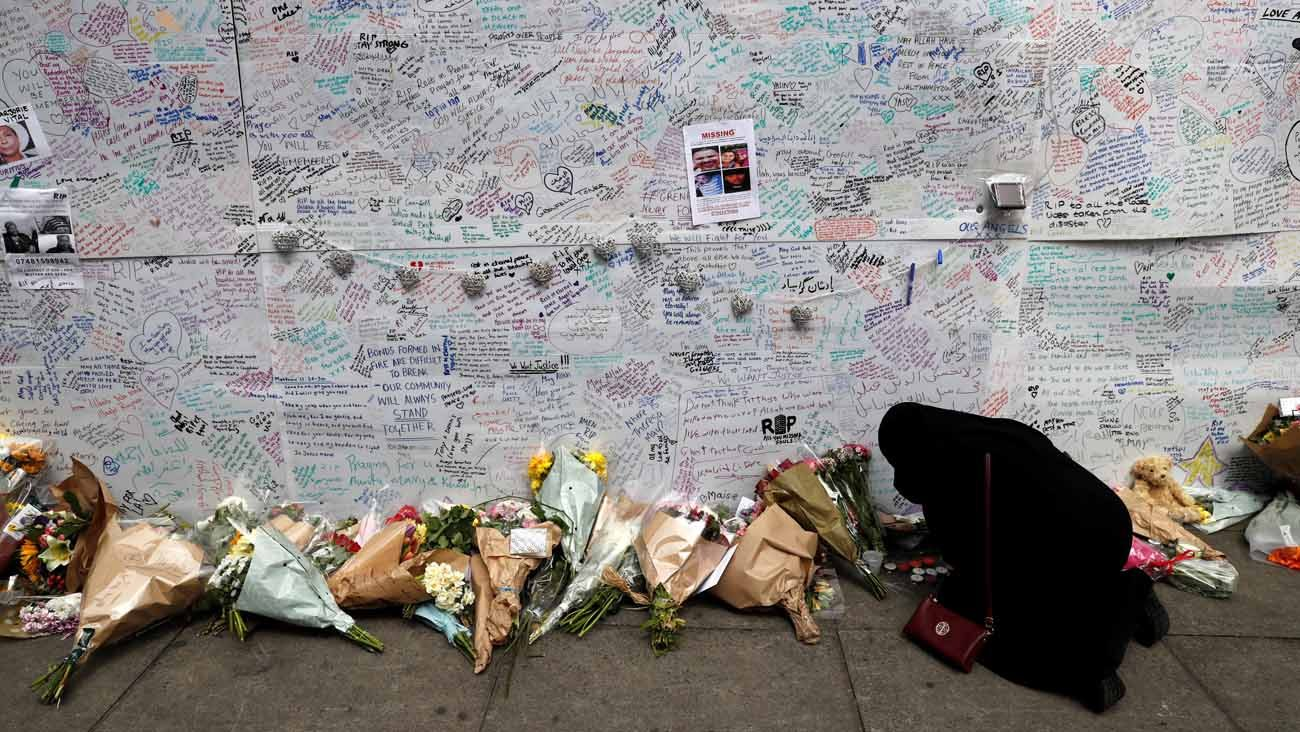 A woman kneels in prayer June 16 beside a message wall near a London apartment building destroyed in a June 14 fire. Church authorities in London confirmed that students from nearby Catholic schools are among the missing from the June 14 fire. (CNS photo/Stefan Wermuth, Reuters)