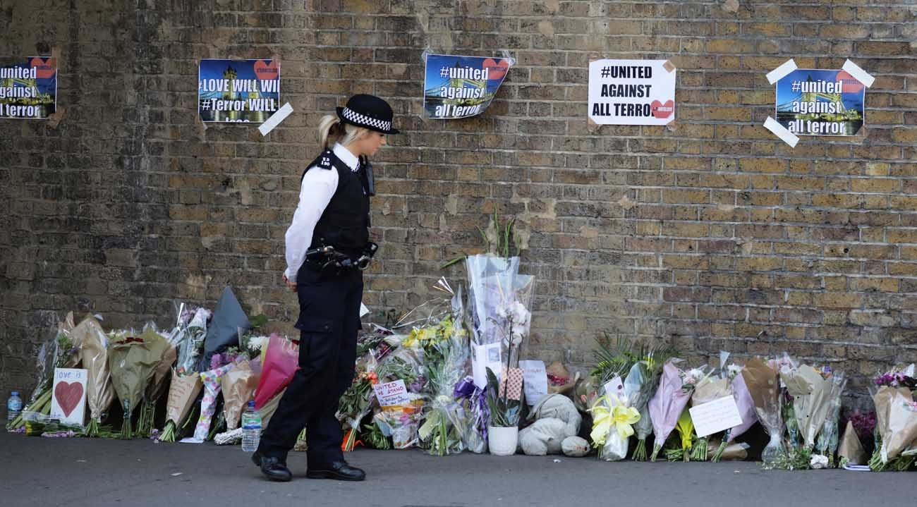 A police officer stands in front of messages and tributes June 19 left near where a man died and 10 people were injured after a van was rammed into a crowd of worshippers near a mosque in north London. A 48-year-old man was arrested in the collision with pedestrians outside the Muslim Welfare House, police said. (CNS photo/Kevin Coombs, Reuters)