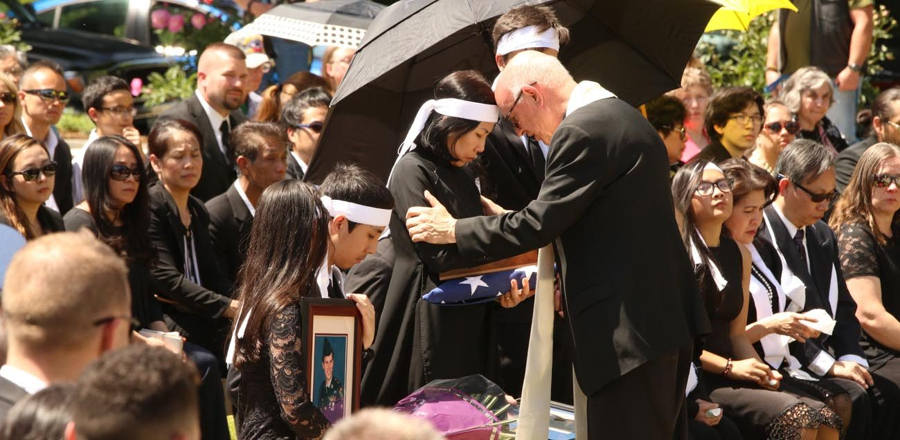 Msgr. Richard Paperini comforts Myhanh Best, wife of Ricky Best, who was killed on a Portland, Ore., commuter train May 26 while defending two girls from an anti-Muslim racist  attack. The ceremony was held June 5 at Willamette National Cemetery in Portland, following a funeral Mass for Ricky Best at Christ the King Church in Milwaukie, Ore. (CNS photo/Ed Langlois, Catholic Sentinel)