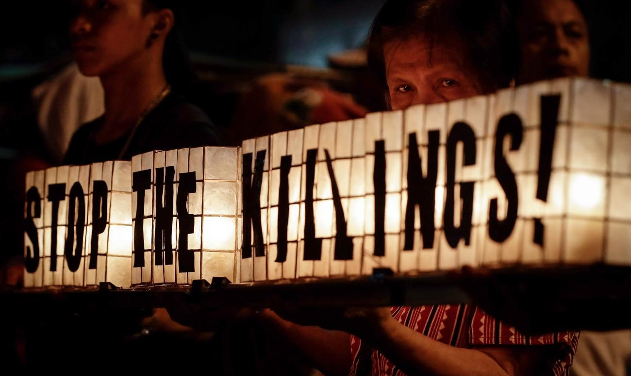 "Activists carry an illuminated sign reading ""Stop the Killings"" during a June 12 protest rally to mark Philippines Independence Day in Manila. The protesters condemn the government's policies on the declaration of martial law and U.S. military intervention in Mindanao.  (CNS photo/Mark R. Cristino, EPA)"