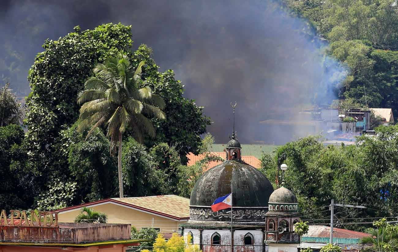 Smoke billows from a burning building near a mosque June 2 as government troops continued their assault on Islamic militants in Marawi, Philippines. Muslim religious and political leaders in the Philippines joined a Catholic bishop in condemning the desecration of a Catholic cathedral by terrorist gunmen in the besieged city. (CNS photo/Romeo Ranoco, Reuters)