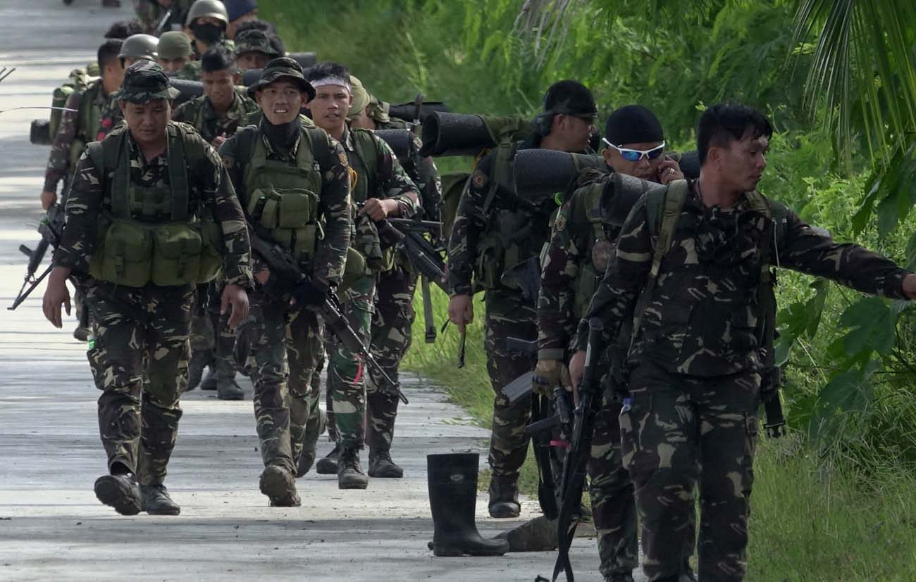 """Government forces of the Philippines patrol a street in Pigcawayan June 22. Father Teresito Soganub, vicar general of the Prelature of Marawi, was seen alive June 25 during a """"humanitarian pause"""" in the conflict. (CNS photo/Cerilo Ebrano, EPA)"""