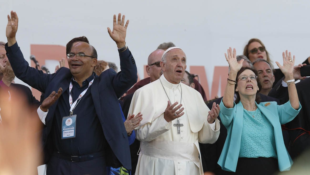Pope Francis prays during a Pentecost vigil marking the 50th anniversary of the Catholic charismatic renewal at the Circus Maximus in Rome June 3. Next to the pope are Gilberto Barbosa from Brazil and Patti Gallagher Mansfield, a participant in the 1967 Pittsburgh retreat that marked the beginning of the Charismatic renewal. (CNS photo/Paul Haring)