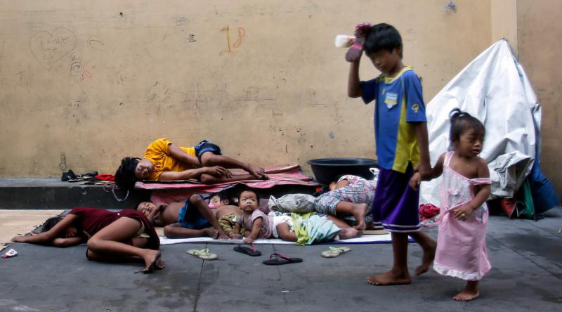 """Homeless Filipinos rest in late April on a street in Manila. World Day of the Poor, to be celebrated Nov. 19 this year, will focus on the apostle John's call to love """"not with words, but with deeds."""" (CNS photo/Francis R. Malasig, EPA)"""