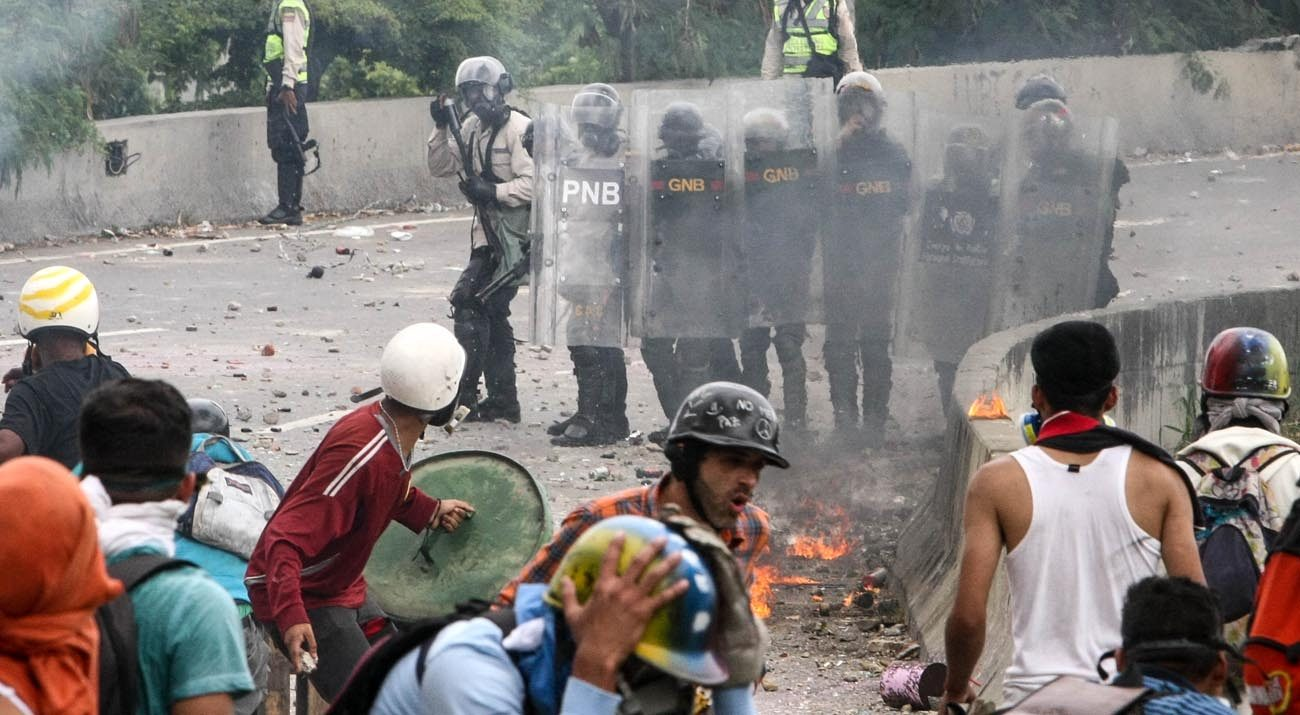 Protesters clash with police June 5  in Caracas, Venezuela. With Venezuela's political and economic crisis turning violent and after the country's president tried to claim he had the support of Pope Francis, the leadership of the country's bishops' conference traveled to the Vatican. (CNS photo/Cristian Hernandez, EPA)