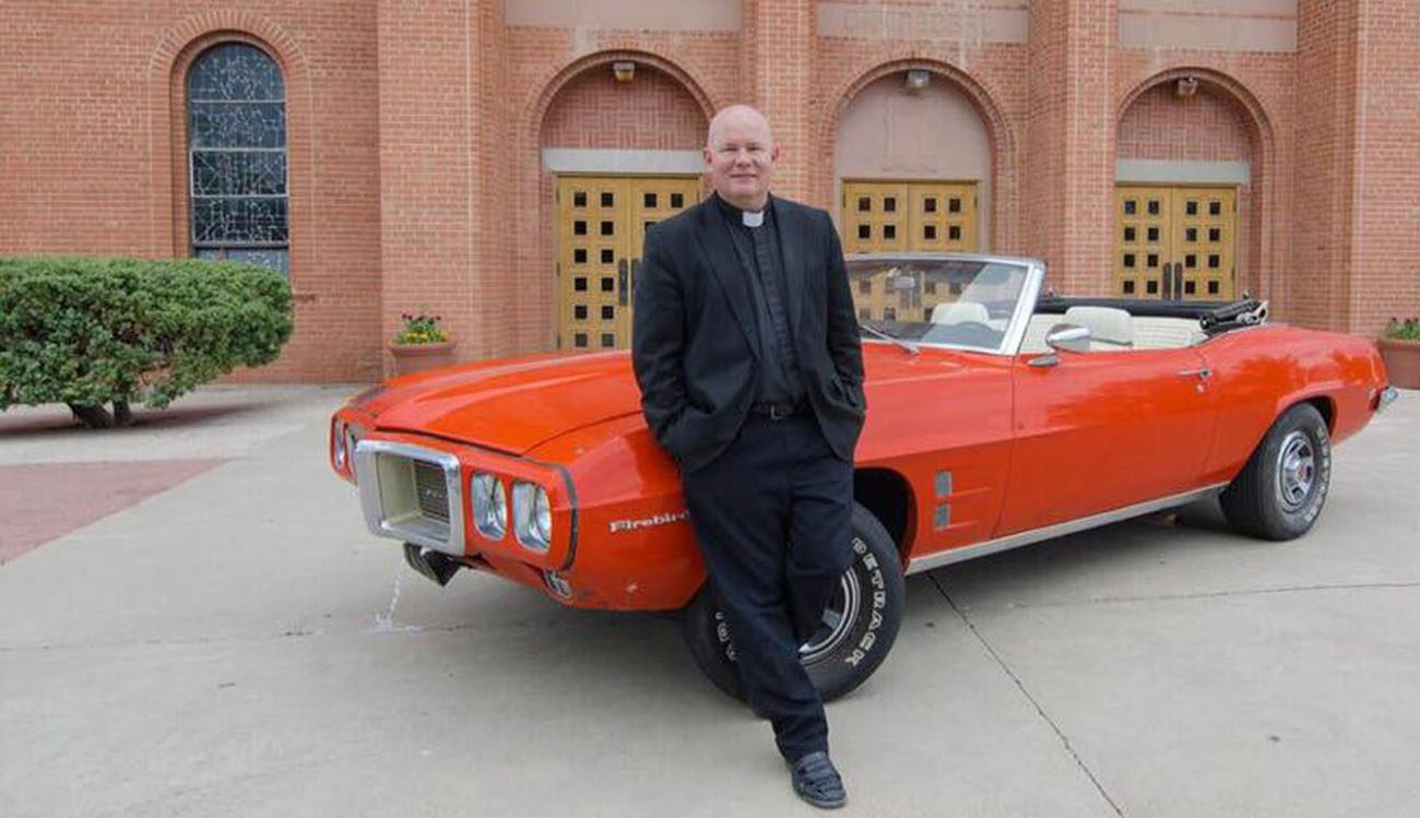Father Matthew Keller, rector of Sacred Heart Cathedral in Gallup, N.M., poses June 8 with a 1969 Pontiac Firebird Convertible that he refurbished for a raffle in support of vocations for the Diocese of Gallup. (CNS photo/V8 for Vocations)