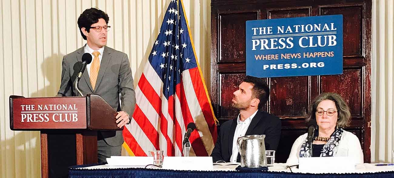 Igor Bobic (seated), associate politics editor for the Huffington Post, listens to Jeremy Robbins of New American Economy speak on a June 19 panel at the National Press club in Washington. The event, held a day before World Refugee Day, was hosted by the U.S. Conference of Catholic Bishops' Migration and Refugee Services. Seated next to Bobic is Pat Maloof, program director of Migration and Refugee Services for the Diocese of Arlington, Va. (CNS photo/Mark Priceman)