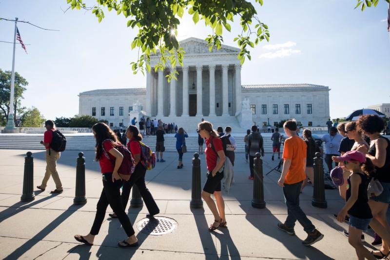 People gather outside the U.S. Supreme Court June 26 in Washington. The high court was issuing its last decisions in its current term, which ends June 30. Two of the most-awaited decisions involved the Trump administration's travel ban and the suit by a Missouri Lutheran preschool denied a state grant for creating a safer playground. (CNS photo/Jim Lo Scalzo, EPA)