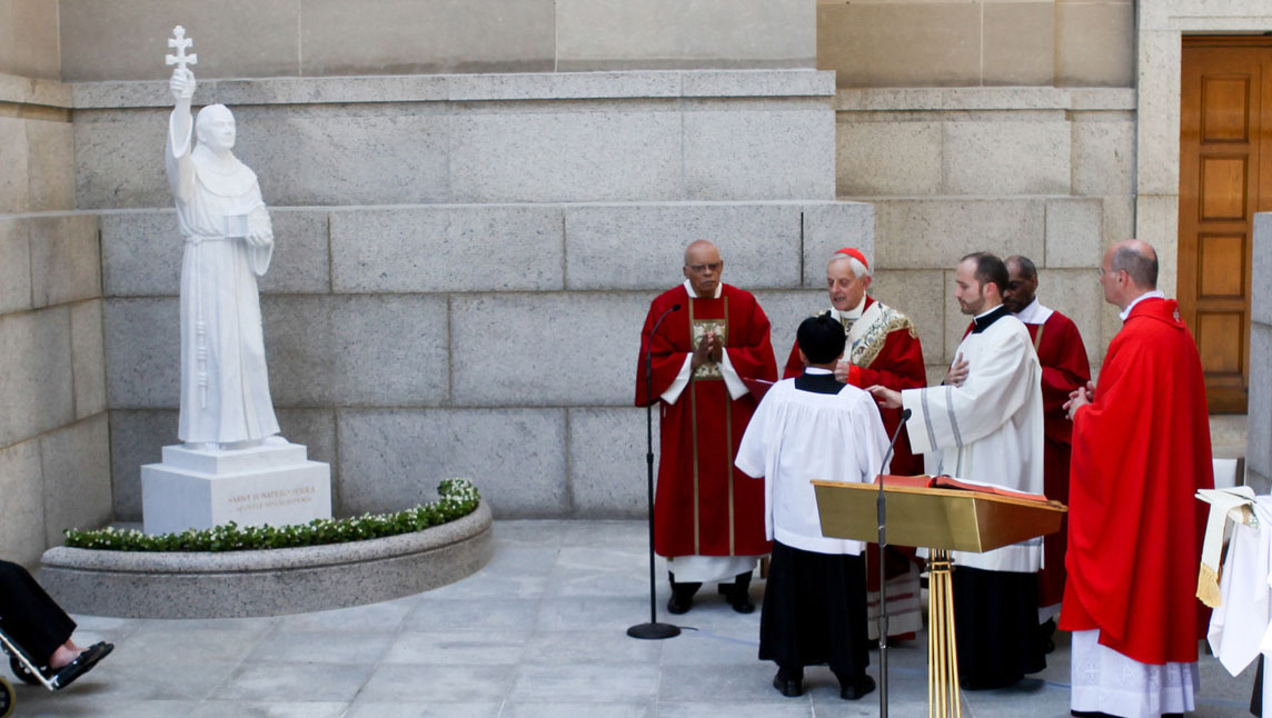 Cardinal Donald W. Wuerl of Washington blesses a new statue of St. Junipero Serra at the Basilica of the National Shrine of the Immaculate Conception in Washington June 4. The statue is located immediately next to the spot where Pope Francis canonized the saint during the pontiff's 2015 visit. (CNS photo/Brian Searby, Catholic Standard)