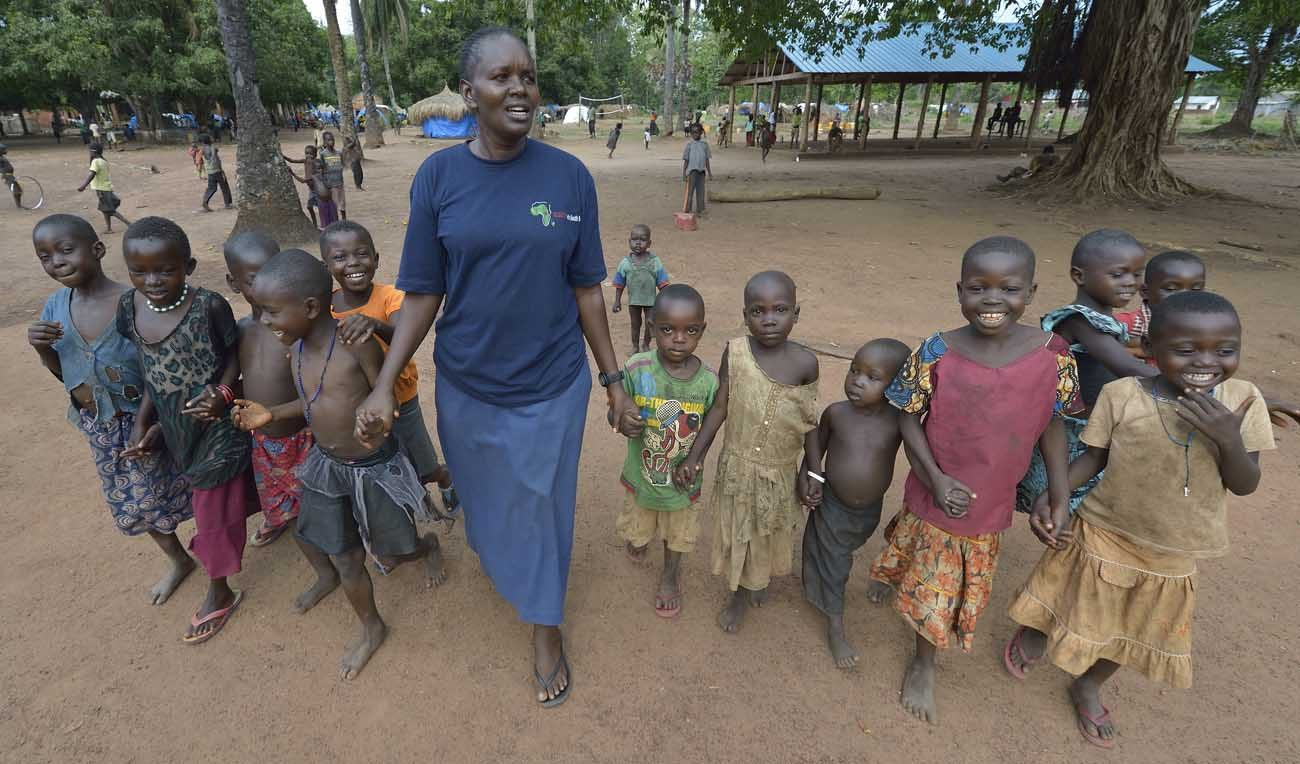 Sister Josephine Murigi, a member of Our Lady of the Missions and Solidarity with South Sudan, walks with children in a camp for more than 5,000 displaced people in Riimenze. Families here were displaced in late 2016 and early 2017 as fighting between government soldiers and rebels escalated. (CNS photo/Paul Jeffrey)