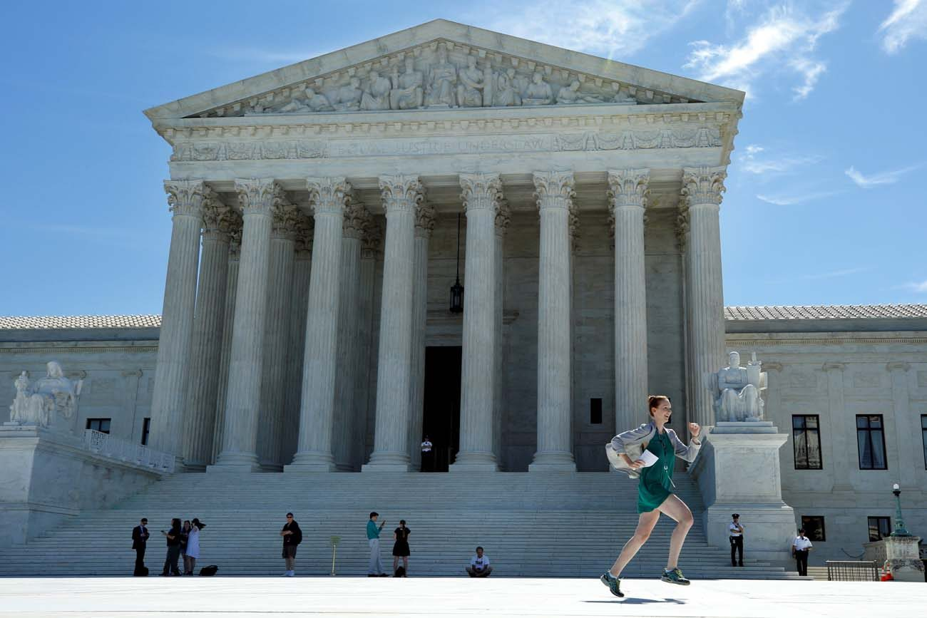 A news assistant runs past the U.S. Supreme Court in Washington after the justices announced they would hear President Donald Trump's travel ban case in October and also said that in the meantime, a limited version of the ban could take effect while the legal battle continues. (CNS photo/Yuri Gripas, Reuters)