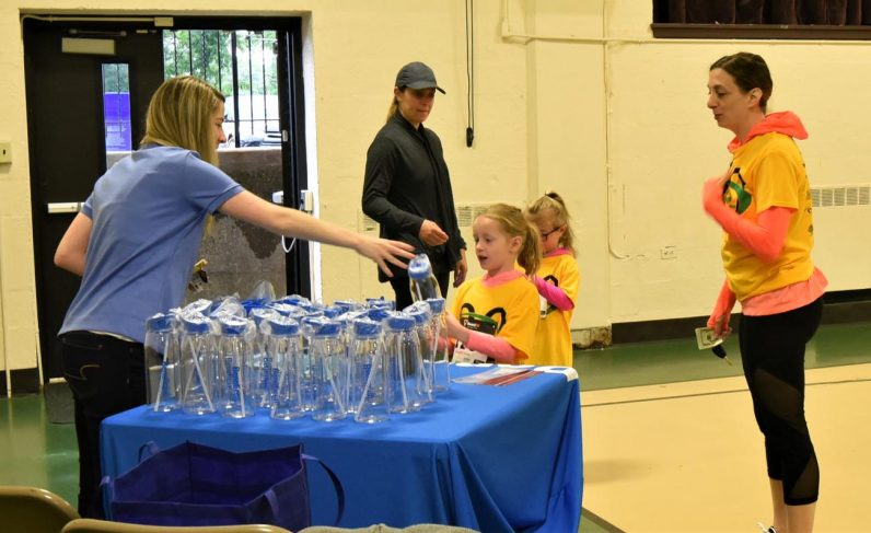 Children receive a free water bottle, courtesy of one of the many vendors at the event.