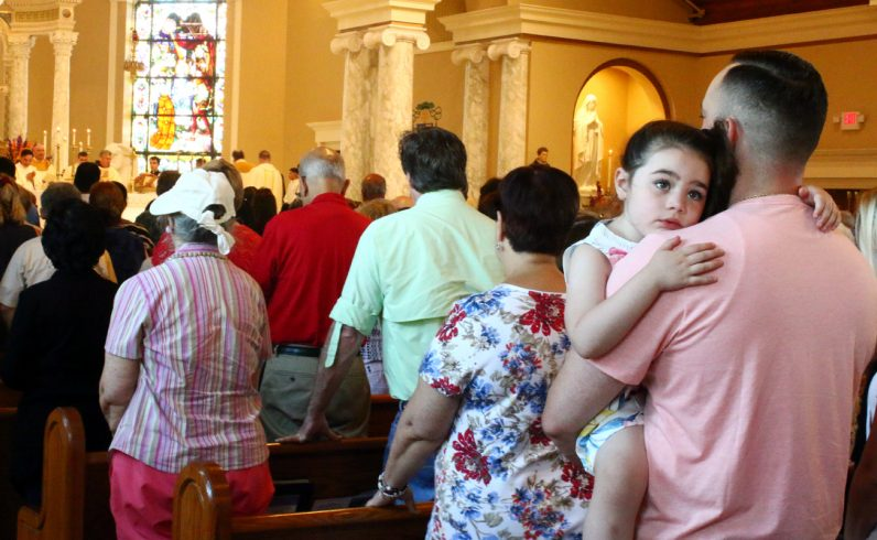 Grace Farrell attends Mass with her father Mitch and her family.