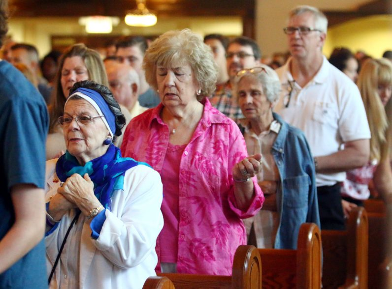 Beatrice Ardovino and Dolores Labrum (left) pray the Lord's Prayer during the Mass at St. Bede Church in Holland preceding a procession through the neighborhood.