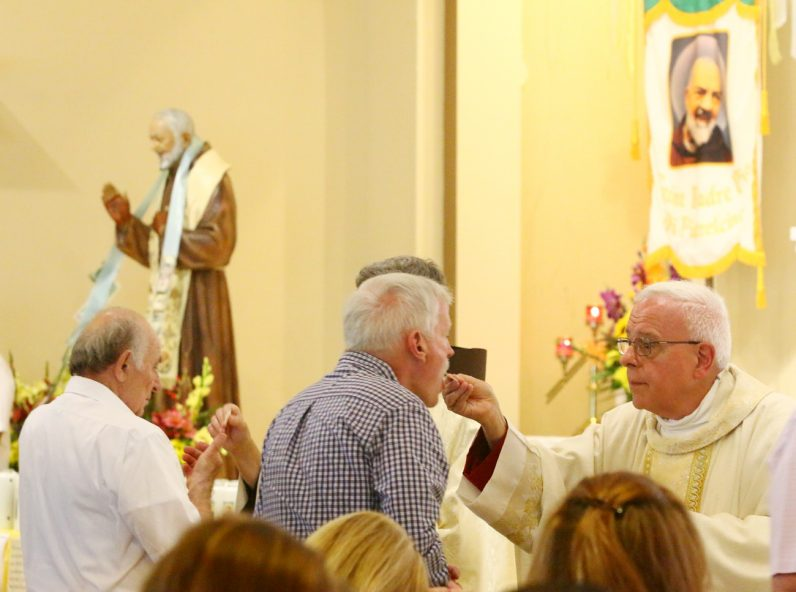 Msgr. John Marine, pastor, distributes holy Communion at St. Bede the Venerable Church, Holland.