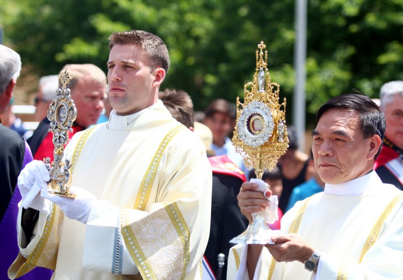 Deacons Kyle Adamczyk (left) and Quy Pham carry the relics of Padre Pio during the procession through the streets around St. Bede the Venerable Church in Holland.