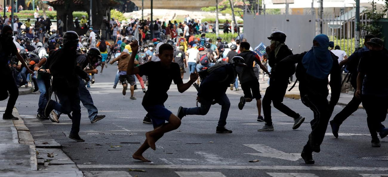 Demonstrators run from security forces during a June 14 rally against Venezuelan President Nicolas Maduro's government in Caracas. (CNS photo/Carlos Garcia Rawlins, Reuters)