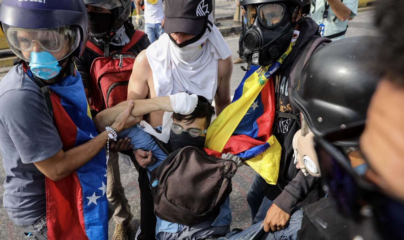 A group of demonstrators tries to help 22 year-old David Jose Vallenilla after he was shot by a Venezuelan military police sergeant June 22 in Caracas. Vallenilla later died from his wounds, bringing to 76 the total number of people killed in the protests. (CNS photo/Miguel Gutierrez, EPA)
