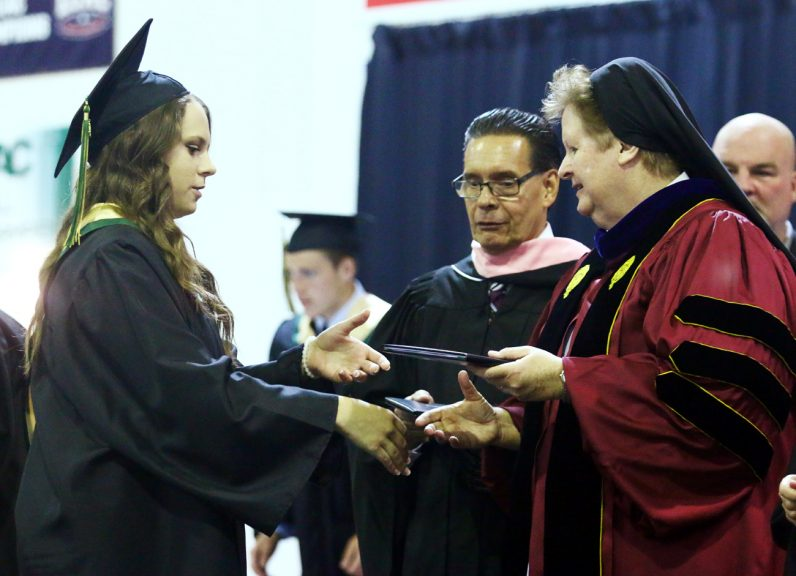 Holly Agnew receives her diploma from Sister Maureen McDermott, I.H.M., during Archbishop Wood graduation ceremony June 5 at Arcadia University.