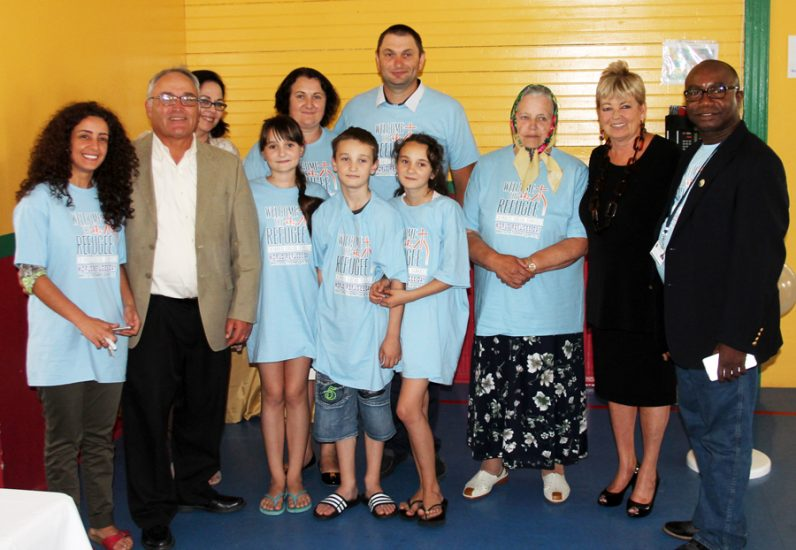 The Dyak family from Ukraine poses with archdiocesan Secretary of Catholic Human Services Jim Amato (second from left), Catholic Social Services' Amy Stoner (second from right), refugee resettlement program coordinator Samuel Abu and other CSS staff June 20 at the Family Services Center in Chester City.