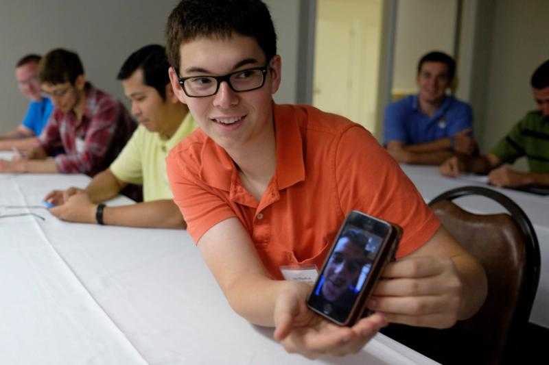 Nashville seminarian Luke Wilgenbusch holds a cellphone Aug. 12, 2014, showing a video link on social media to a fellow seminarian. Pope Francis' Twitter proves daily that the Gospel's message can be shared in less than 140 characters. (CNS photo/Rick Musacchio, Tennessee Register)