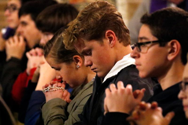 Teenagers pray during a Holy Hour for vocations Jan. 20 at St. Patrick Church in Bay Shore, N.Y., sponsored by the vocations office of the Diocese of Rockville Centre, N.Y. Attracting and building young adult ministries requires social skills, sometimes musical skills, a strong knowledge of the basics of Christian faith and Catholic beliefs, and a warm appreciation of the unexpected. (CNS photo/Gregory A. Shemitz, Long Island Catholic)