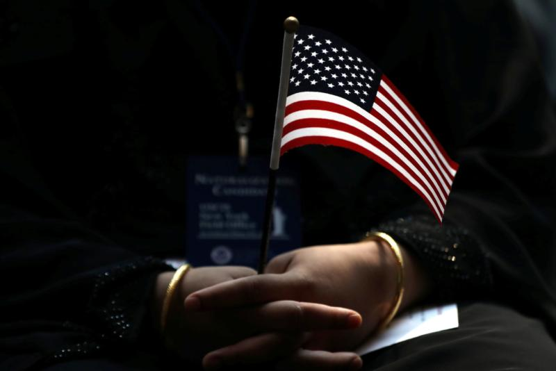 An immigrant holds a U.S. flag during a naturalization ceremony in New York City June 30. (CNS photo/Shannon Stapleton, Reuters)
