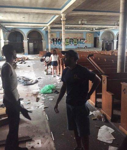In the lower church of the former Ascension of Our Lord Church in Philadelphia's Kensington section, addicted squatters talk on a recent morning.
