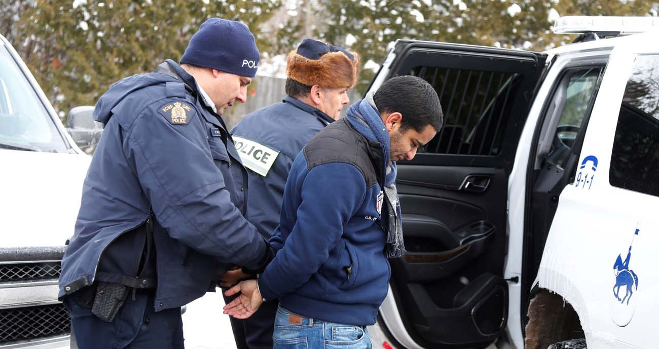 A man who told police he was from Mauritania is taken into custody Feb. 14 by Royal Canadian Mounted Police officers after walking across the U.S.-Canada border into Quebec. (CNS photo/Christinne Muschi, Reuters)
