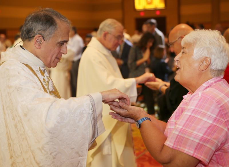 "Cardinal Daniel N. DiNardo of Galveston-Houston, president of the U.S. Conference of Catholic Bishops, and Los Angeles Archbishop Jose H. Gomez, who is vice president of USCCB, distribute Communion during the closing Mass July 4 at the ""Convocation of Catholic Leaders: The Joy of the Gospel in America"" in Orlando, Fla. Leaders from dioceses and various Catholic organizations gathered for the July 1-4 convocation. (CNS photo/Bob Roller)"