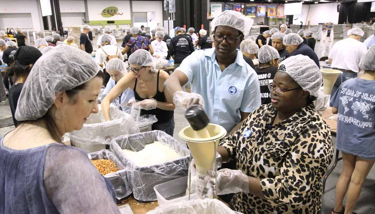 Jean Sawadogo and his wife, Pauline, fill a bag with rice during the Atlanta Archdiocese's Eucharistic Congress in College Park, Ga., June 16. They are parishioners of St. John Neumann Church in Lilburn, Ga. (CNS photo/Michael Alexander, Georgia Bulletin)