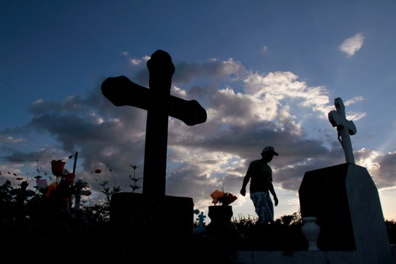 "A man visits the graves of deceased relatives at a cemetery in Managua, Nicaragua. In the Nicene Creed we profess that we ""look forward to the resurrection of the dead and the life of the world to come."" (CNS photo/Oswaldo Rivas, Reuters)"