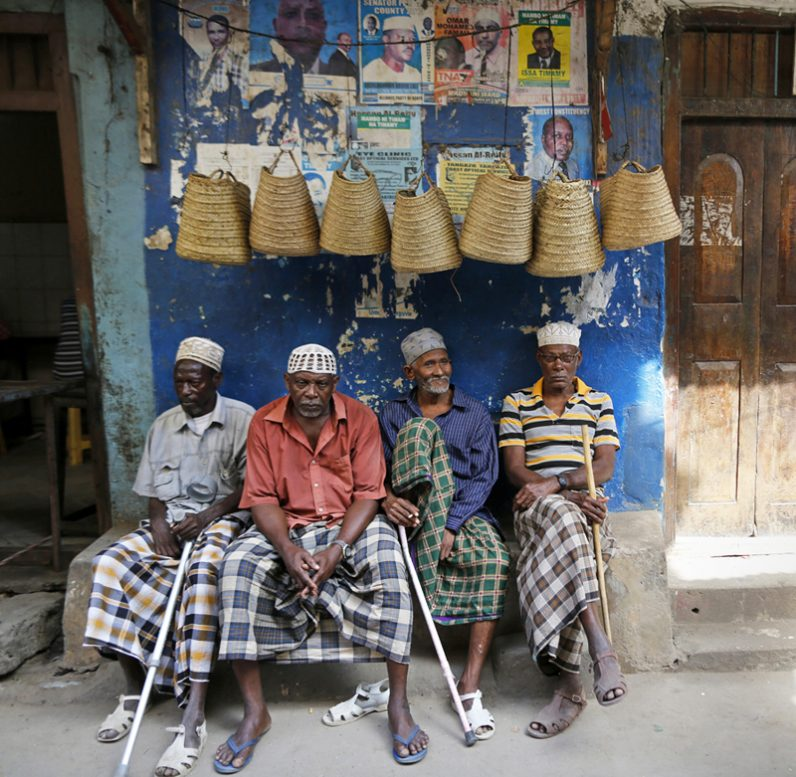 Elderly men sit on a bench in front of souvenir shops in Lamu, Kenya, in this 2014 file photo. Suspected al-Shabab militants have increased attacks in the area, forcing locals to flee into churches. (CNS photo/Dai Kurokawa, EPA)