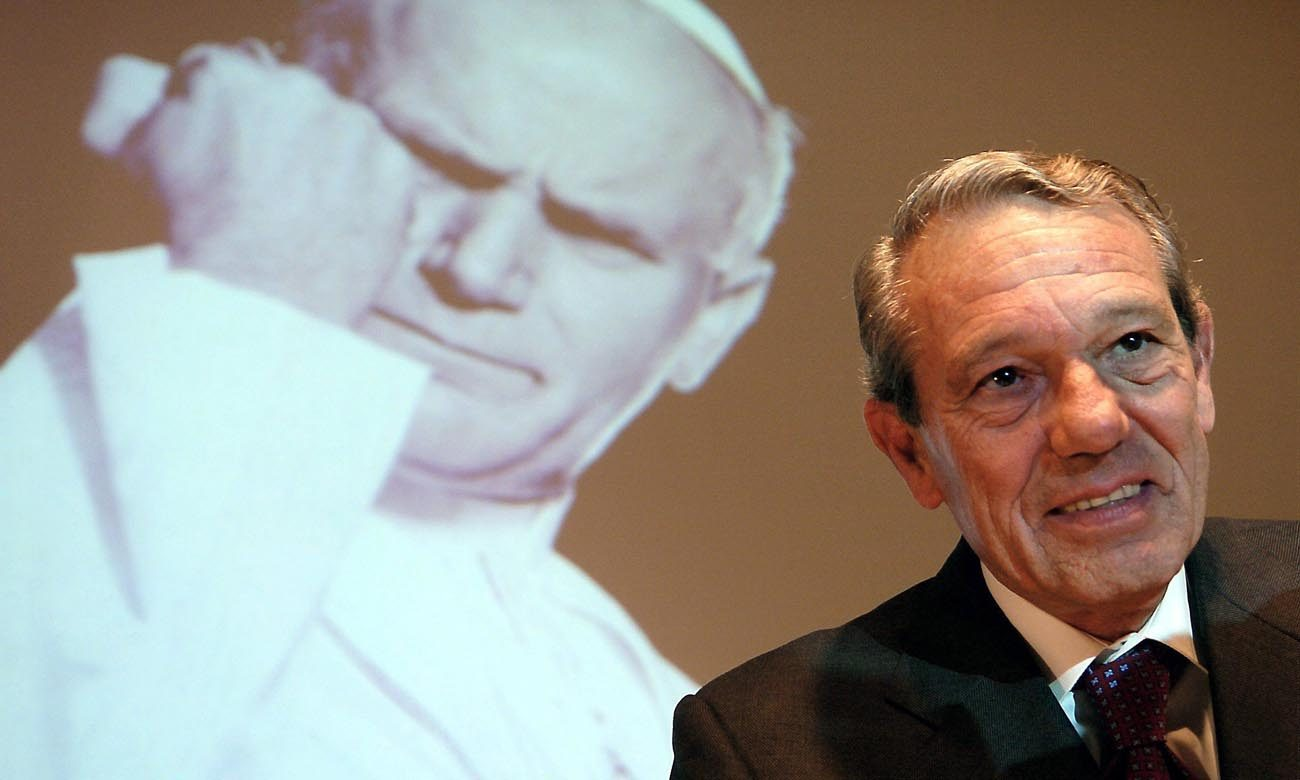 Joaquin Navarro-Valls, who spent 22 years as director of the Vatican press office, died July 5 at age 80. He is pictured speaking in 2004 alongside a projected image of St. John Paul II. (CNS photo/Arne Dedert, EPA)